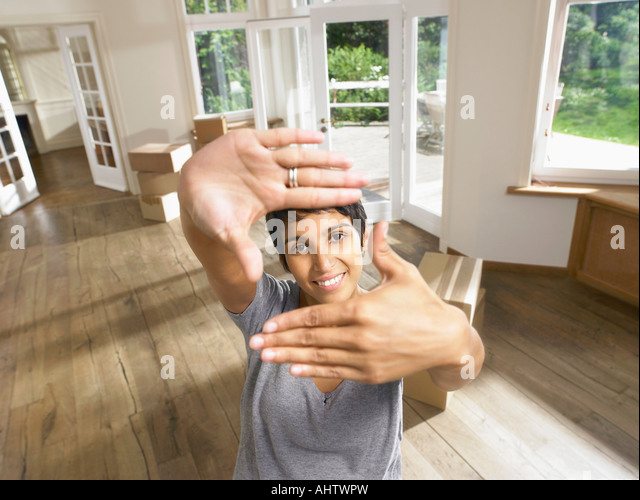Woman framing face with hands moving into empty house. - Stock Image