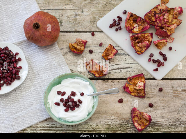whole pomegranate, peel and seeds with bowl of yogurt on rustic table - Stock Image
