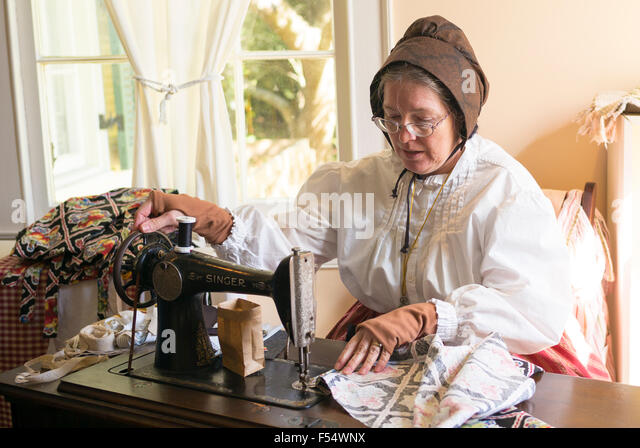 Craftsperson with sewing machine at Vermilionville history museum of Acadian, Creole, Native American cultures, - Stock-Bilder
