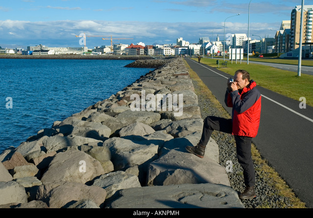 Tourist taking a photograph on the waterfront, Reykjavik, Iceland - Stock Image