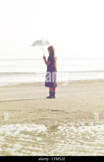 Girl on the beach with umbrella - Stock Image