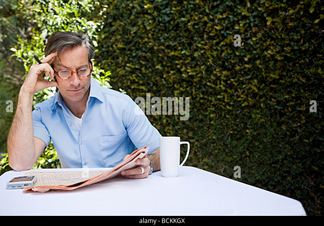 Man outdoors with newspaper - Stock Image
