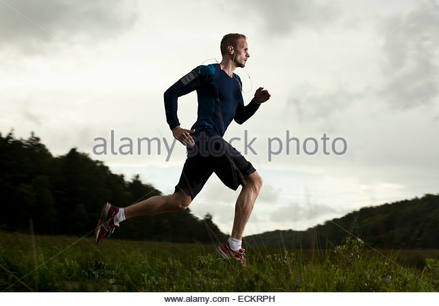 Full length side view of determined man running on grassy field against cloud sky - Stock Image
