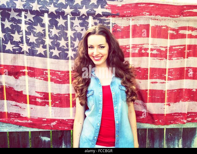 Young Woman Smiling In Front Of Us Flag - Stock Image
