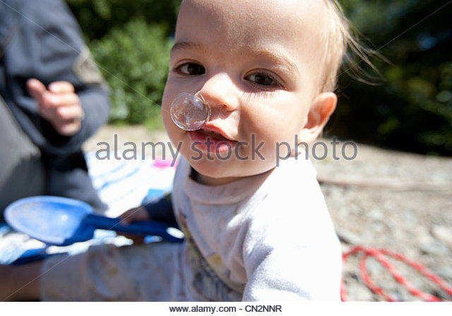 Toddler boy with bubble coming out of nose - Stock Image