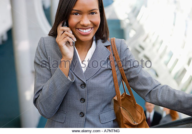 Businesswoman with handbag standing on escalator using mobile phone smiling front view portrait elevated view - Stock Image