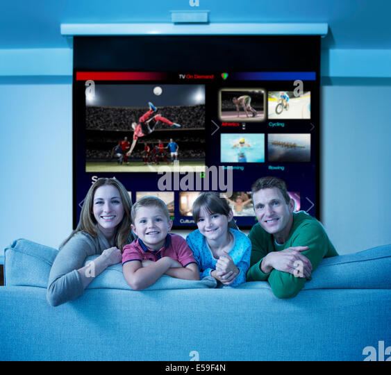 Family watching multi screen television in living room - Stock Image