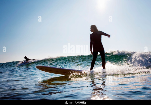 Man and woman surfing. - Stock Image