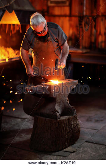 Authentic Old-Fashioned Blacksmith forging red hot molten iron with hammer on the anvil in his old workshop - Stock Image