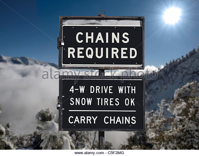 Chains or snow tires required sign with mountain backdrop. - Stock-Bilder