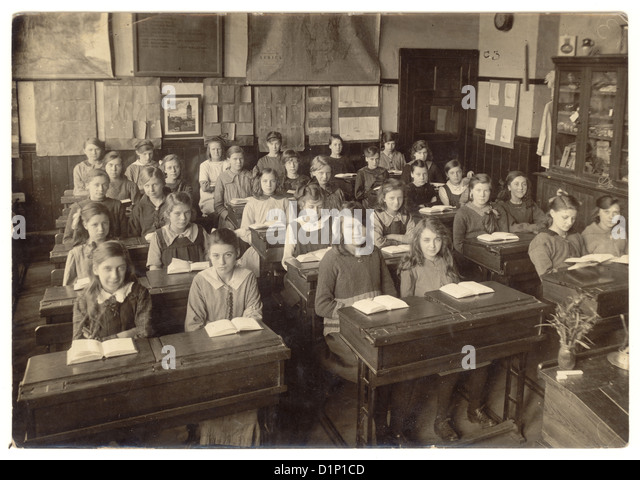 School photograph of junior girls sitting at their desks, with open books in classroom - 1930's, U.K. - Stock Image