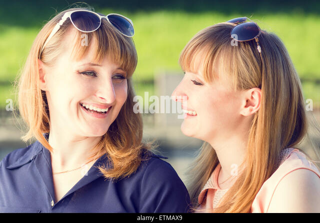 Young twins girls having fun laughing in summer park. Pretty students sister with sunglasses talking each other. - Stock Image