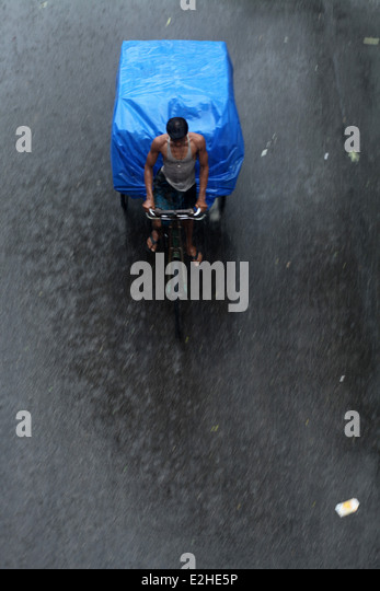 A labor carrying good using wooden cart during rain. - Stock Image