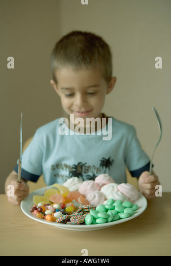 Little boy holding knife and fork looks at a plate full of sweets that look like a meal - Stock Image