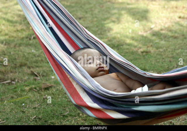 1 year old Asian baby sleeping on a hammock - Stock Image