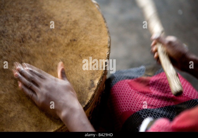 Leading the children's church choir by beating a rhythm with hand and stick on a drum. - Stock Image