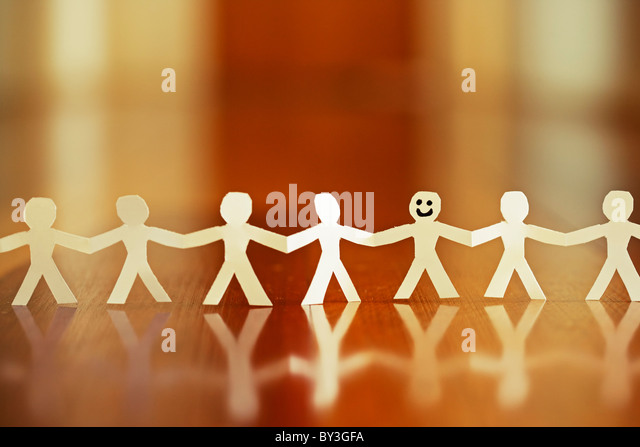 Smiling paper chain man stands out from the crowd - Stock Image