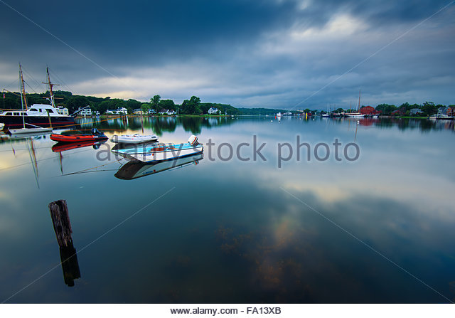 Scenic calm and peaceful river scene at Mystic Connecticut with cloud reflections in the water and boats - Stock Image