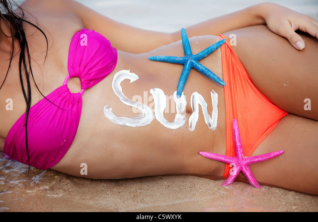 part of female sunbathing, the word 'sun' is written with sun screen - Stock Image