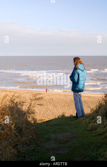 Girl watching the sea Thorpeness Suffolk England - Stock Image
