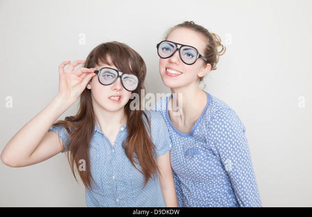 Two girls wearing fake glasses - Stock Image