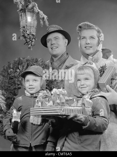 1950s 1960s FAMILY BY LANTERN CARRYING WRAPPED CHRISTMAS PRESENTS - Stock Image