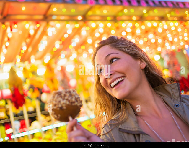 Woman holding caramel apple at funfair - Stock Image