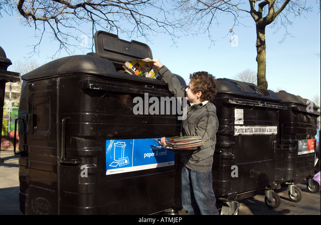 Young child putting paper into recycling bins, London, England UK - Stock Image
