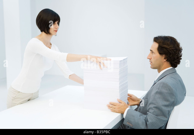 Professional woman and businessman exchanging tall stack of paper across desk - Stock Image