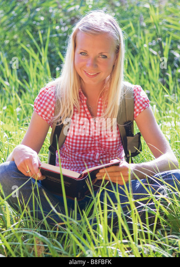 Young woman sitting on grass while reading a book - Stock Image