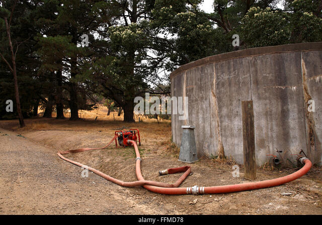 Concrete water storage tank with pump and hoses, Victoria Australia - Stock Image