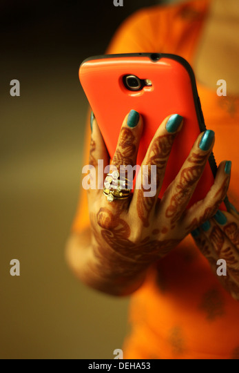 Portrait of young attractive woman checking cell phone - Stock Image