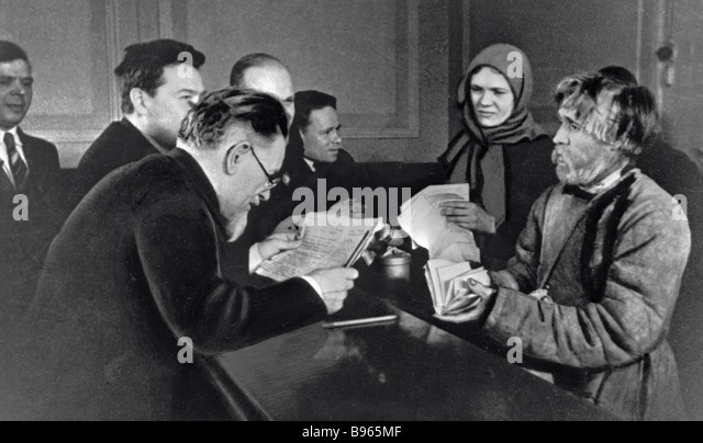 Chairman of the USSR Supreme Soviet Mikhail Kalinin left talking to petitioners in his reception office - Stock Image