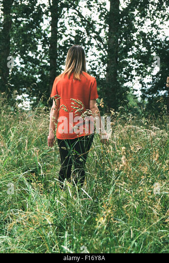 Woman walking through a field  of long grass - Stock-Bilder