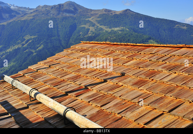 Traditionally-tiled roof in Switzerland, using wooden shakes as roof tiles. Wood is either pine or cedar - Stock-Bilder