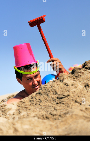 crazy man is joking on the beach in the sand with a rake and a bucket - Stock Image