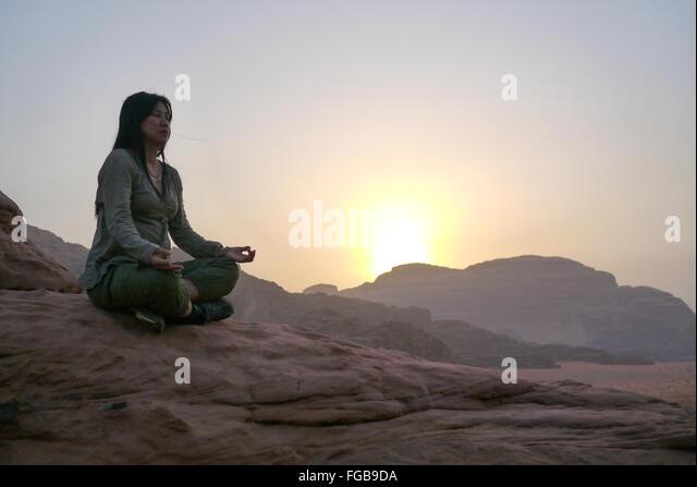 Woman Meditating At Desert Against Sky During Sunrise - Stock Image
