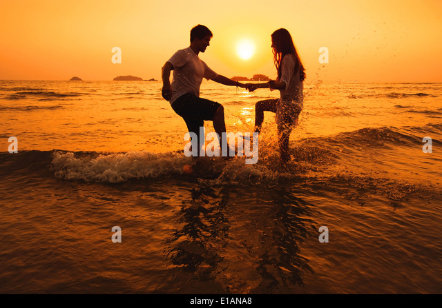 couple having fun in the sea at sunset beach - Stock Image