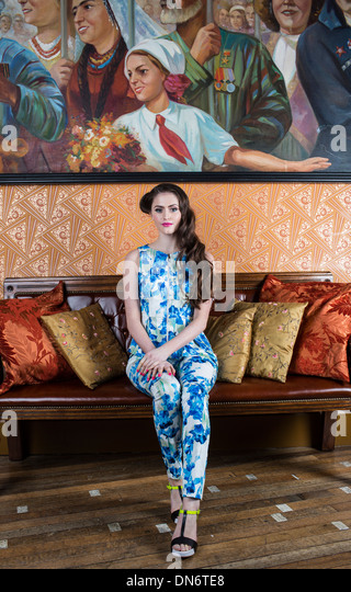 A teenage brunette girl wearing a blue and white flower patterned jump-suit. - Stock-Bilder