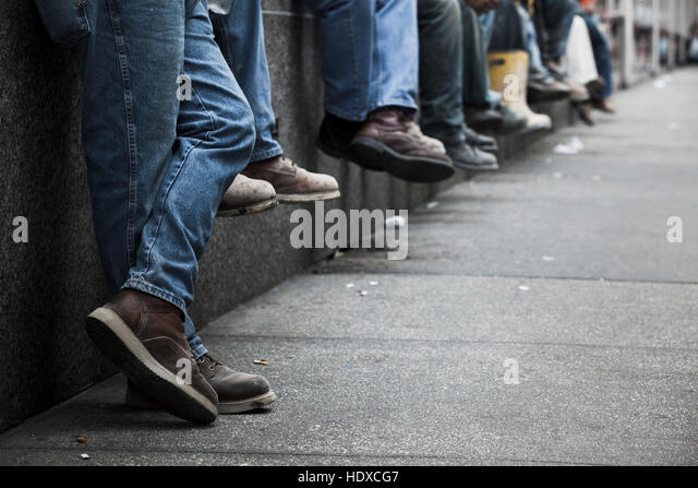 Closeup of workers boots and jeans lined up along a wall - Stock-Bilder