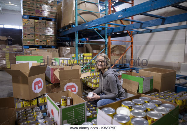 Portrait confident female volunteer filling donation boxes with canned food for food drive in warehouse - Stock Image
