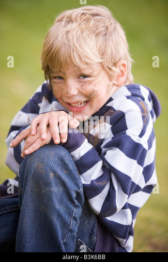 Young boy sitting outdoors dirty and smiling - Stock Image