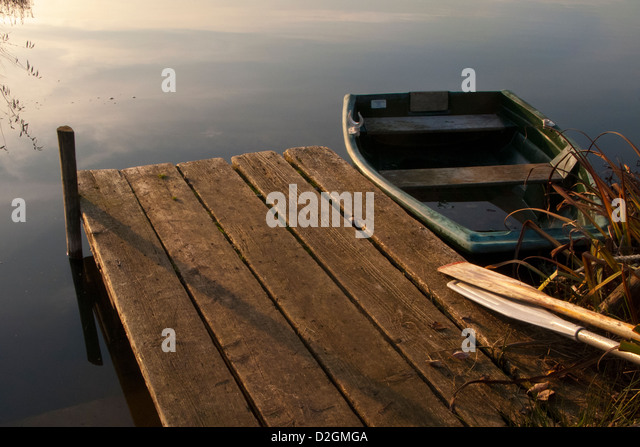 Wooden Jetty pier by lakeside in late afternoon light with rowing boat and wood oars - Stock Image