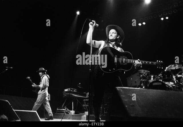 Rock group U2 performing on stage at the National Exhibition Centre in Birmingham. Pictured is lead singer Bono - Stock Image