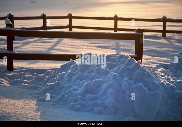 Pile of snow near fence - Stock Image