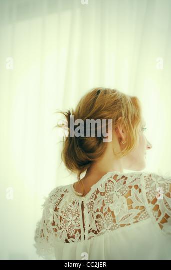 USA, New Jersey, Jersey City, Woman looking out window - Stock-Bilder