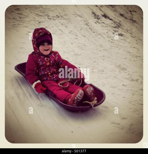 Girl sled riding in winter. - Stock Image