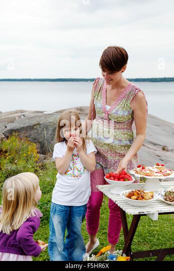 Sweden, Uppland, Roslagen, Woman preparing picnic table at seaside - Stock Image