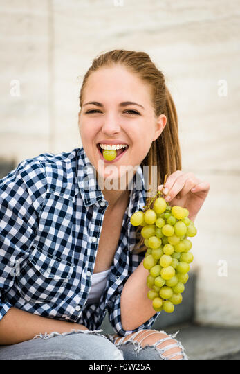 Young woman eating grapes outdoor - holding grape between teeth - Stock Image