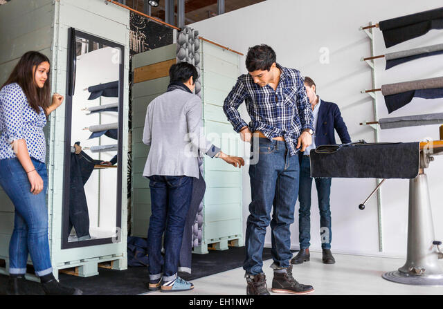 Woman looking at man trying jeans in factory - Stock Image